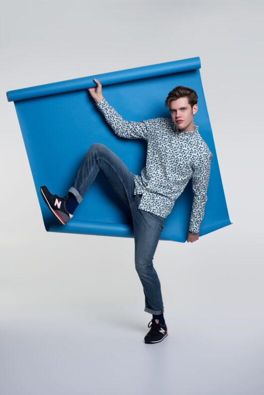 A white and blue casual button down long sleeve shirt with an all over blueberry print worn by a handsome young man holding a roll of blue paper