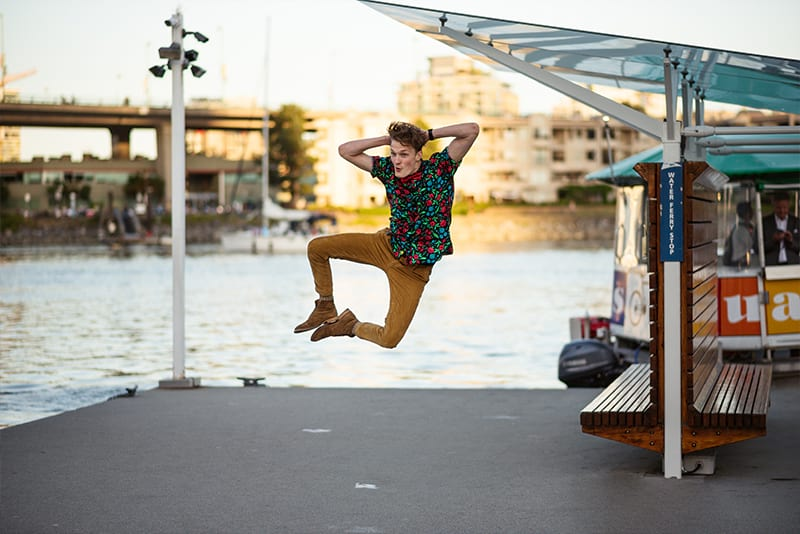 A young man jumping in the air wearing a hawaiian floral casual button down shirt