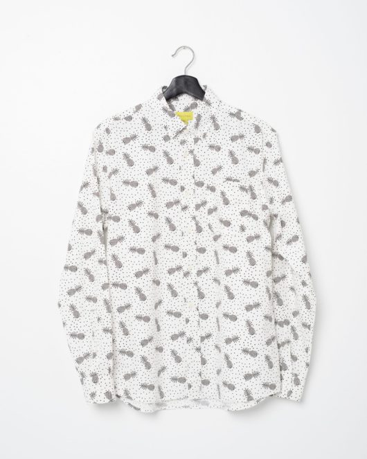 A product flat of a white and black casual button down long sleeve shirt covered with pineapples and polka dots