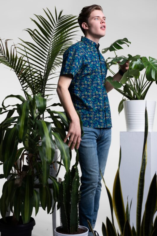 A floral blue yellow and green casual button down short sleeve shirt worn by a handsome young man surrounded by tropical plants