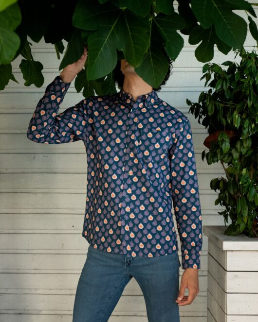 A blue and purple casual button down long sleeve shirt covered with abstract figs worn by a handsome young man with his head stuck in a fig tree