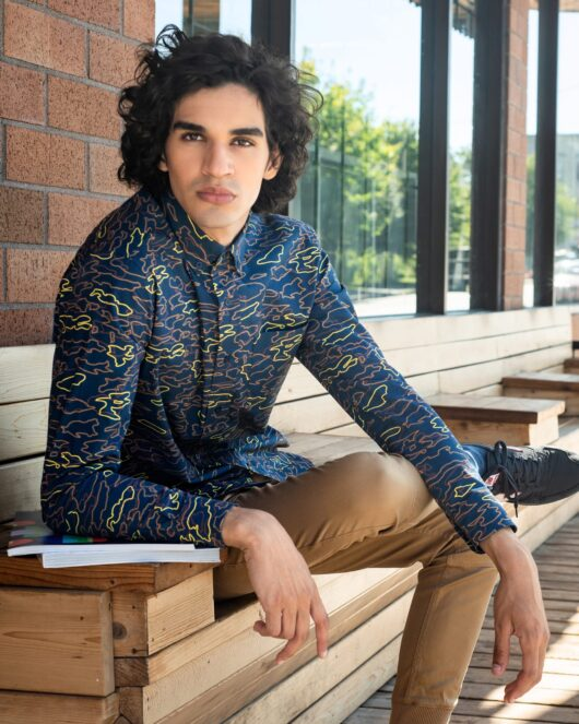 A navy casual button down long sleeve shirt with an all over geometric camo print worn by a handsome young man sitting at a cafe