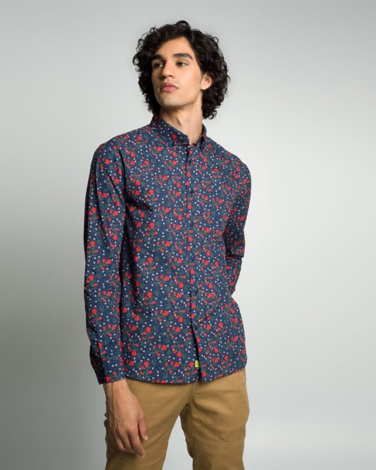 A floral navy casual button down long sleeve shirt with an all over red floral print worn by a handsome young man in brown joggers