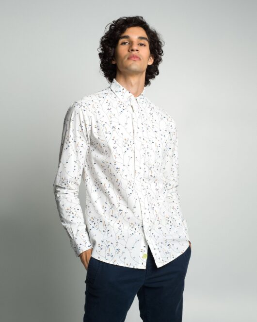 A floral white casual button down long sleeve shirt with an all over floral vine print worn by a handsome young man in blue joggers