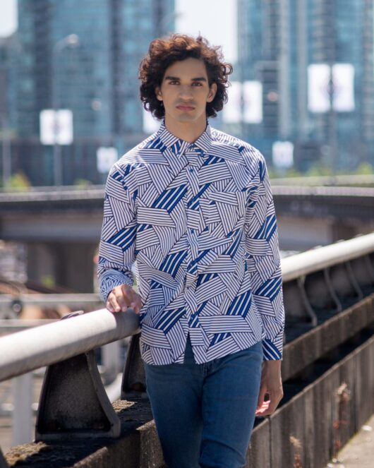 A white and blue casual button down long sleeve shirt with an all over stripe print worn by a handsome young man walking on a bridge