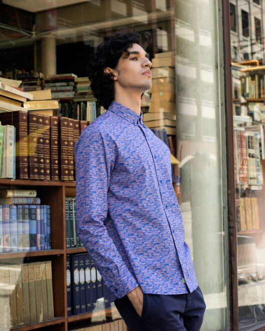 A blue and pink casual button down long sleeve shirt with an all over owl print worn by a handsome young man leaning against a bookstore display window