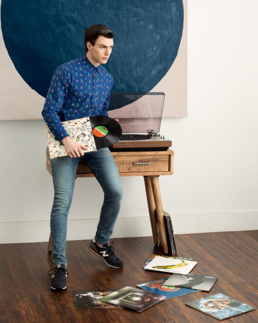 A blue casual button down long sleeve shirt with an all over hawaiian print worn by a handsome young man sitting by a record player while holding a record
