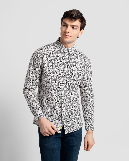 A floral white and black casual button down long sleeve shirt covered with flowers worn by a handsome young man in dark blue jeans