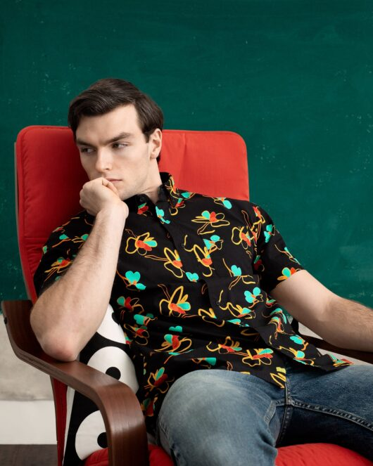A hawaiian casual button down short sleeve shirt covered with red, blue, yellow and green flowers worn by a handsome young man sitting in a chair