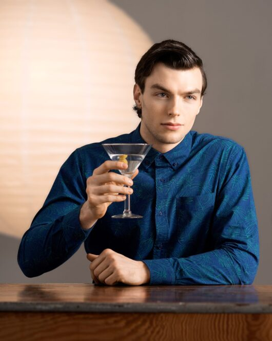 A navy casual button down long sleeve shirt covered with a green monstera outline all over print worn by a handsome young man holding up a martini while sitting at a wood table