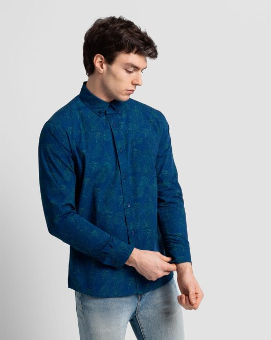 A navy casual button down long sleeve shirt covered with a green monstera outline all over print worn by a handsome young man in light blue jeans