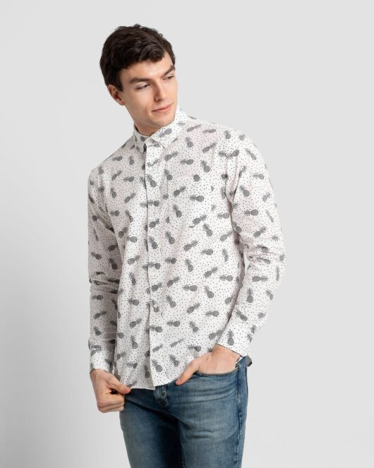 A white and black casual button down long sleeve shirt covered with pineapples and polka dots worn by a handsome young man in blue jeans
