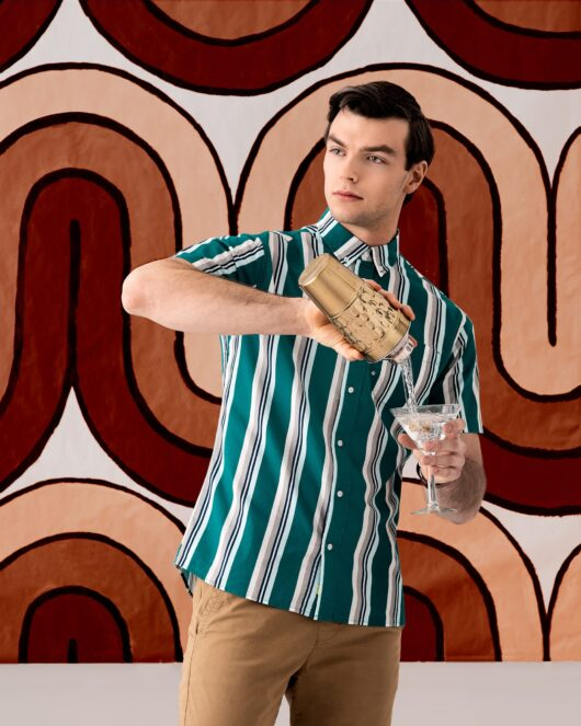 A casual button down short sleeve shirt with green, white, grey and blue stripes worn by a handsome young man in brown khakis standing in front of groovy retro painting pouring a martini