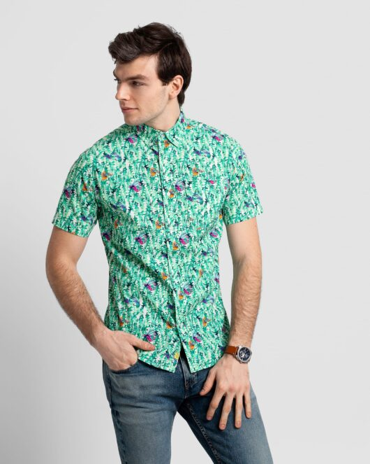 A green colored casual button down short sleeve shirt with an allover seaweed and fish print worn by a handsome young man in blue jeans